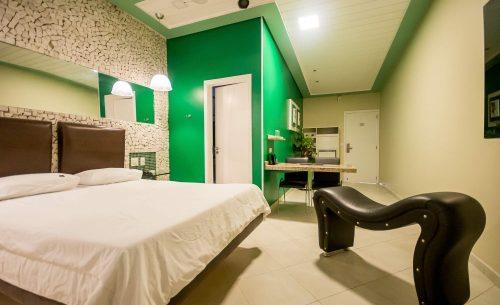 img-suite-super-luxo-parede-verde-espreguicadeira-belle-motel